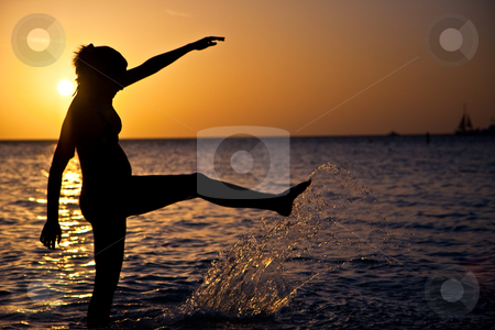 Splash! stock photo, Pregnant woman splashes in the water, silhoutted at sunset. by Tyson Koska