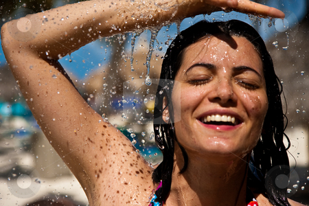 Waterfalling stock photo, A woman showers poolside at a beach in Aruba. by Tyson Koska