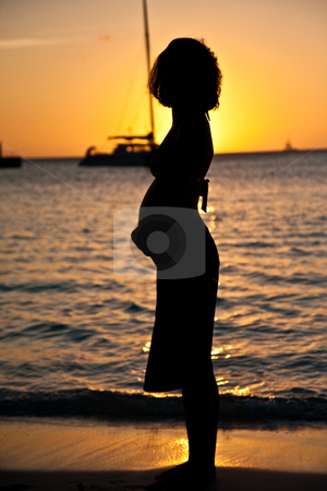 Pregnancy and Sunset stock photo, Pregnant woman watches the sunset at the beach. by Tyson Koska
