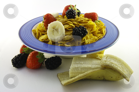 Cornflakes and Fruit in a Blue Bowl with Banana stock photo, Cornflakes with strawberries, blackberries and banana in a round blue bowl on a white background by Keith Wilson