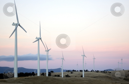 Wind Farm at Sunset stock photo, Wind generators sit separated along the hilltops of a modern wind farm by Lee Torrens