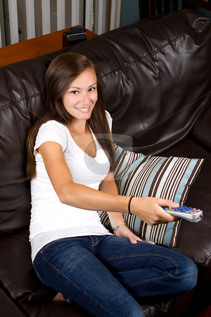 Teenage Girl at Home stock photo, Girl at Home watching tv with a remote control by Mehmet Dilsiz