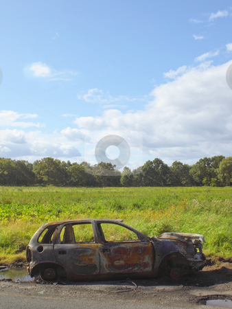 Burnt out car stock photo, A burnt out car by a roadside in summer by Mike Smith