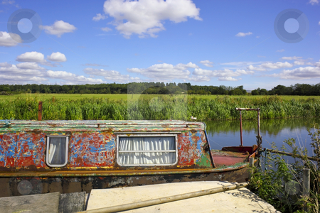 Summer on the river stock photo, A weathered narrow boat on a river on a beautiful summers day by Mike Smith