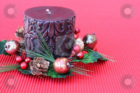 Berry Christmas Wreath stock photo, Dark pattern candle with a wreath on a red background by Vanessa Van Rensburg