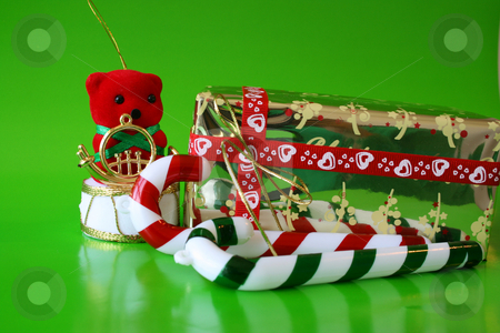Christmas Deco stock photo, Christmas decorations on a green background with a wrapped present by Vanessa Van Rensburg