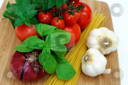 Raw Spaghetti Ingredients stock photo, Fresh herbs and vegetables to make spaghetti, including red onion, tomatoes, basil, oregano, garlic and dry pasta. by Lynn Bendickson