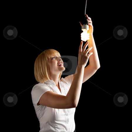 Attractive Blonde Turning on Lightbulb stock photo, An attractive blonde touching a lightbulb. Square framed shot. by Media Deva
