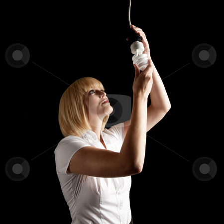 Attractive Blonde Changing Lightbulb stock photo, An attractive blonde changing a lightbulb. Square framed shot. by Media Deva