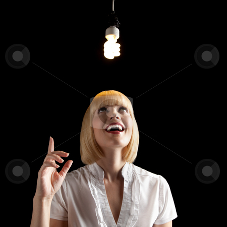 Beautiful Blonde with Light Fixture stock photo, A beautiful blonde standing in a dark room.  She is smiling and pointing upward toward a hanging light fixture.  Square framed shot. by Media Deva