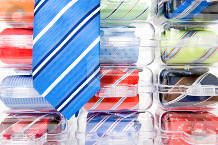 Neckties stock photo, A blue striped necktie, hanging over a display with plastic gift packs containing an assorted array of other ties by Corepics VOF
