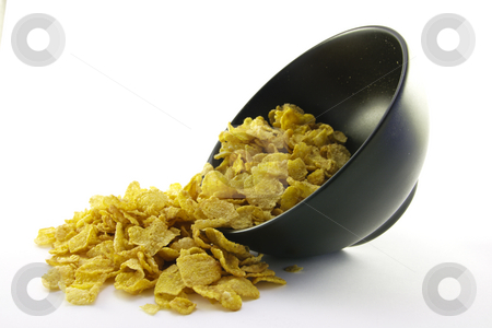 Cornflakes Spilling out of a Bowl stock photo, Golden cornflakes spilling out of a round black bowl on a white background by Keith Wilson