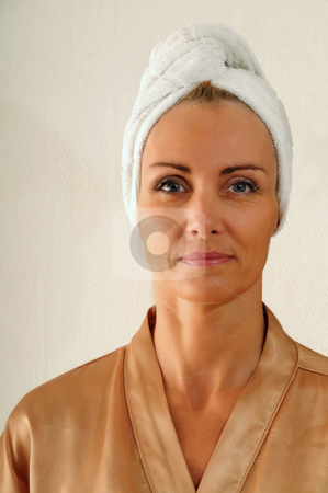 Woman in bathrobe stock photo, Woman in bathrobe with towel around her head. by Tony Lott N??rnberger
