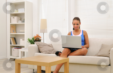 Girl and laptop stock photo, Young woman sitting in sofa using laptop by Tony Lott N??rnberger