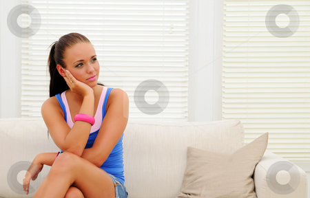 SofaGirl stock photo, Young woman sitting on sofa by Tony Lott N??rnberger