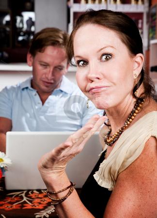 Man using laptop ignoring his date in coffee house stock photo, Handsome man using laptop ignoring his pretty date in coffee house by Scott Griessel