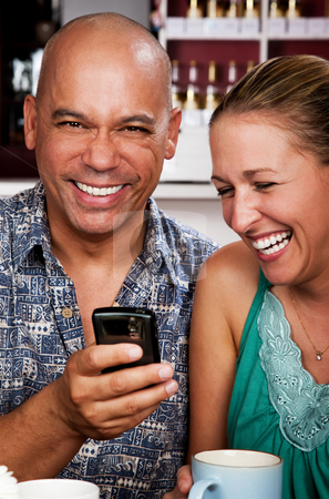 Couple in Coffee House with Cell Phone stock photo, Attractive couple in a coffee house with cell phone by Scott Griessel