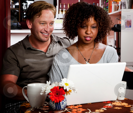 Mixed race couple in coffee house with laptop computer stock photo, Caucasian man and African American woman in coffee house with laptop computer by Scott Griessel