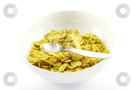 Cornflakes in a Bowl stock photo, Golden cornflakes in a white bowl with a spoon on a white background by Keith Wilson