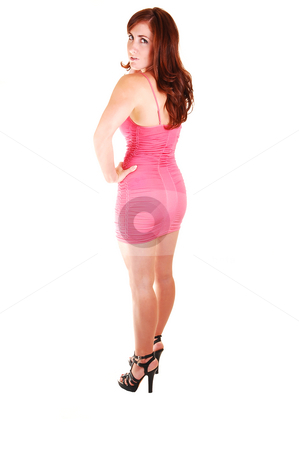Pretty girl in pink short dress. stock photo, Young, lovely girl in a short pink dress with red hair, looking over her shoulder and high heels standing in the studio for white background. by Horst Petzold