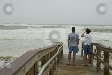 Gustav Walkway Spectators stock photo, PENSACOLA - SEP 1: A couple watches the raging surf from an elevated walkway during Hurricane Gustav on September 1, 2008. Gustav made landfall in Lousiana only 1 mph below a Cat 3. by A Cotton Photo