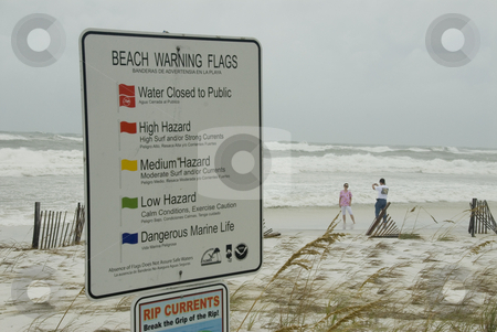 Quaking Sign stock photo, PENSACOLA - SEP 1: A couple takes photos of the incoming surf while a warning sign quakes in the wind during Hurricane Gustav on September 1, 2008.  Gustav reached winds of 150 mph. by A Cotton Photo