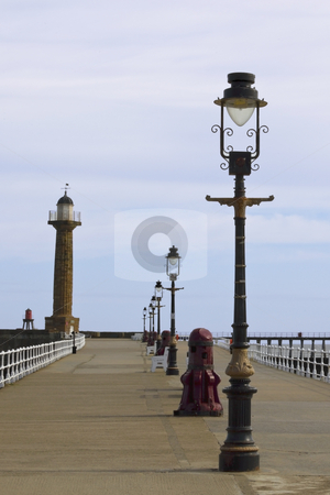 Old lamps stock photo, Old lamps and a light tower on a pier by Mike Smith