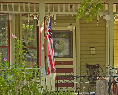 Americana Doorway Porch stock photo, This doorway porch area is Americana themed with an American flag hanging on porch rail. by Valerie Garner