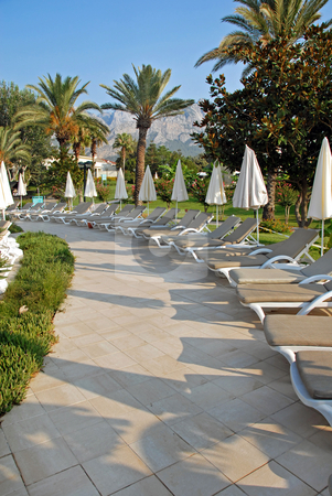 Road by swimming pool chairs in resort in Turkey stock photo, Empty chairs in resort Kemer in Turkey by palms outdoor by Julija Sapic