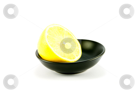 Half a Lemon stock photo, Half a juicy yellow lemon in a small black dish on a white background by Keith Wilson
