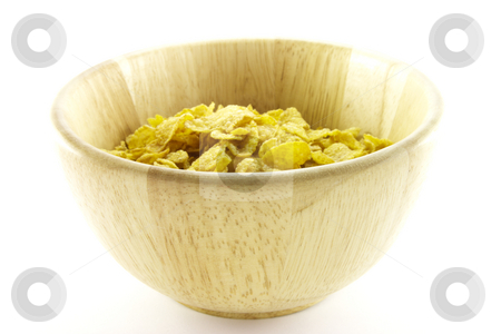 Cornflakes in a Bowl stock photo, Golden cornflakes in a wooden bowl with a white background by Keith Wilson