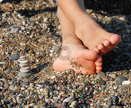 Rocks stack and boy feet stock photo, Child feet next to rocks stack on beach by Julija Sapic