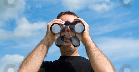 Man Using Binoculars Outside stock photo, A young man looking at the viewer with a set of binoculars, with a blue sky behind him by Richard Nelson