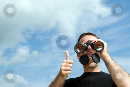 Thumbs Up stock photo, A young man gives a thumbs up as he holds a set of binoculars to his eyes, with clouds and blue sky behind him by Richard Nelson