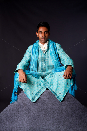 Hindu man sitting in lotus position stock photo, Beautiful authentic Indian hindu man in typical ethnic groom attire sitting in lotus position with legs crossed on top of rock. Bangali male wearing a light blue agua decorated Dhoti with shawl. by Paul Hakimata