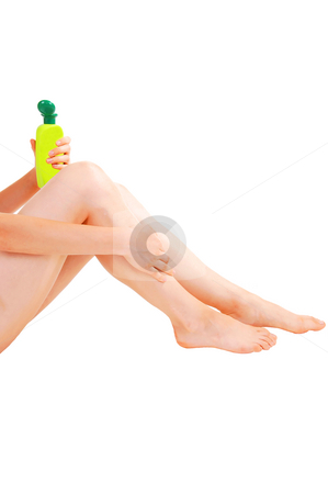 Woman taking care of her skin. stock photo, A young pretty girl sitting on the floor after the shower and taking care of her skin on the legs, for white background. by Horst Petzold