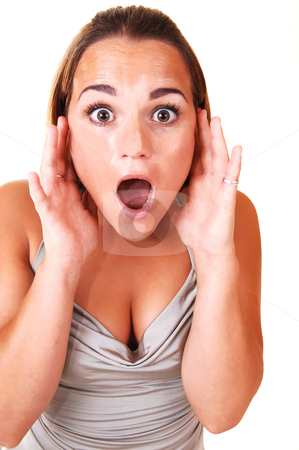 Pretty girl screaming. stock photo, Young, lovely girl in a silver dress, screaming with her eyes wide open standing in the studio for white background. by Horst Petzold