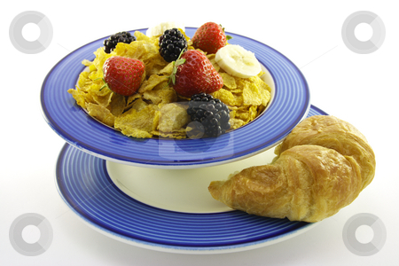 Cornflakes and Fruit with Croissant stock photo, Cornflakes with strawberries, blackberries and banana in a round blue bowl with a croissant on a plate with a white background by Keith Wilson