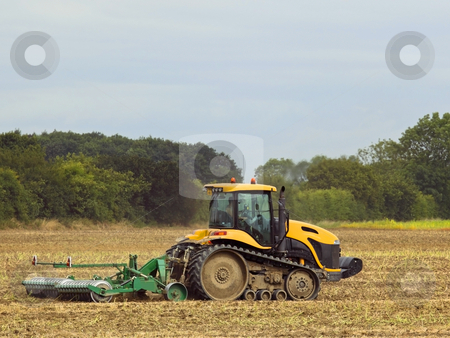 Yellow tractor stock photo, A yellow tractor rolling a field by Mike Smith
