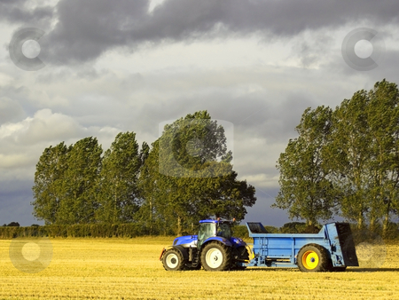Manure spreading stock photo, A blue tractor spreading manure on a stubble field by Mike Smith