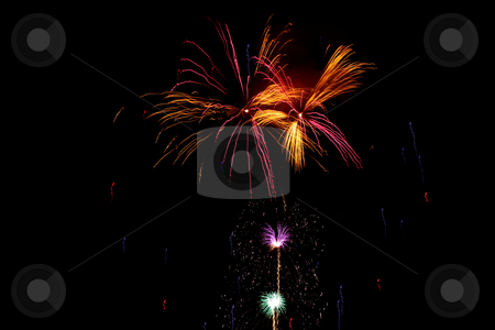 Multiple bursts of green, gold, pink, red, blue and purple firew stock photo, Multiple bursts of green, gold, pink, red, blue and purple fireworks light the night sky by Stephen Goodwin