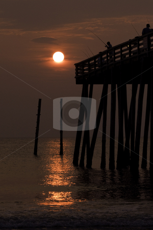 Silhouette of a boy fishing from a pier at sunrise stock photo, Silhouette of a boy fishing from a pier in Kitty Hawk, NC at sunrise by Stephen Goodwin