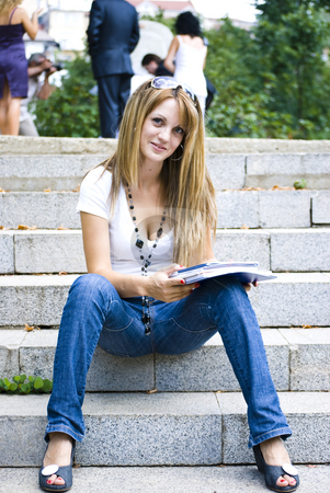 Beautiful young woman reading book stock photo, Beautiful young woman reading book outdoor by Desislava Dimitrova