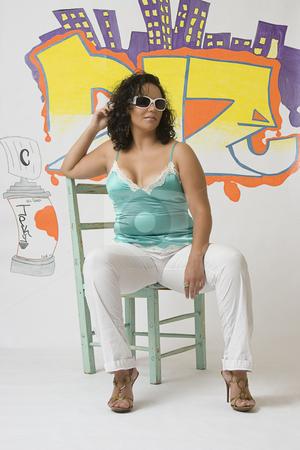 Latino women stock photo, Twenty something latino women sitting in front of graffitied wall by Yann Poirier