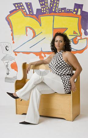 Latino women stock photo, Twenty something latino women sitting on a bench front of a graffiti by Yann Poirier