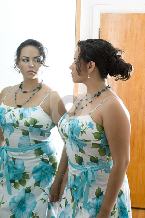 The women in the mirror stock photo, Latino women looking at herself in a doorway mirror by Yann Poirier
