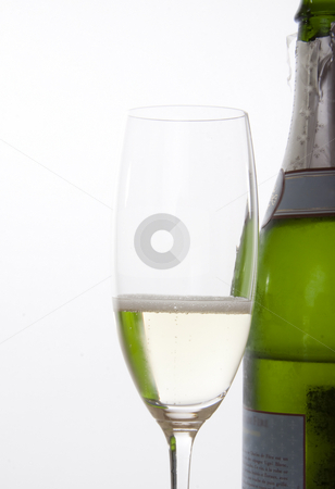 Champagne glass and bottle stock photo, Glass of champagne and a bottle in the background by Daniel Kafer