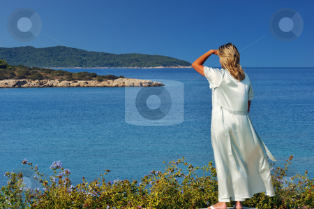 Morning view of the islands stock photo, A blond beautiful woman is gazing at the spectacular view of the Greek islands during a clear morning of her summer holidays by Andreas Karelias