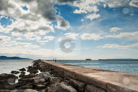 Romantic walk on the pier stock photo, A couple in the distance strolling along the pier in Kalamata, southern Greece, under a spectacular cloudscape by Andreas Karelias