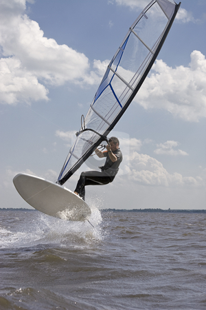 Windsurfer jumping stock photo, Windsurfer doing a jump trick in the water by Yann Poirier